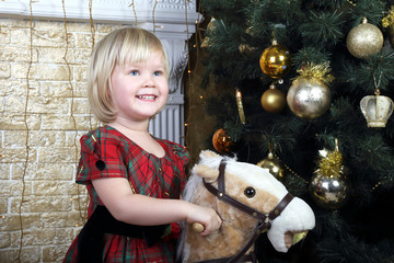 blonde little girl sits on a toy horse near Christmas tree