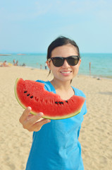 Young woman holding slice of watermelon and smiling while standi