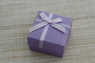 Purple gift box on textured background. Selected focus.