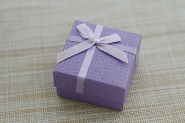 Purple gift box on textured background. Soft focus to give a touch of magical.