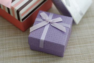 Gift boxes on textured background. Selected focus emphasized on purple box.