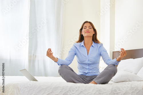 business frau macht yoga auf bett im hotel stock photo and royalty free images on. Black Bedroom Furniture Sets. Home Design Ideas