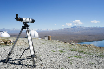 telescope and observatory on ground near lake in summer day in n