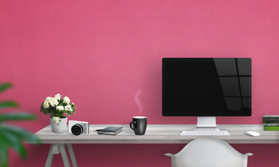 Computer with blank screen on office desk. Free space on wall for text. Pink wall in background.