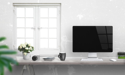 Computer with blank screen on office desk. Window and white wall in background.