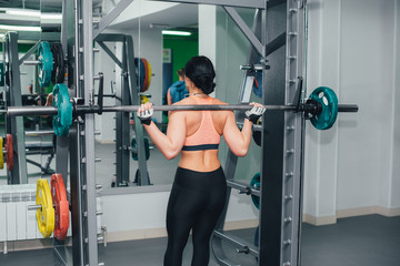 The girl goes in for sports in the gym