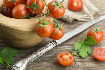 Heap of cherry tomatoes in bowl, with knife and some cut in half, on wooden surface.