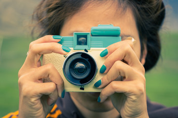 young adult woman with a retro camera
