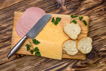Sliced sausage, cheese and bread with knife