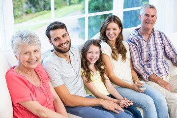 Portrait of smiling family sitting on sofa