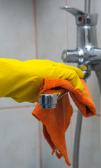 Closeup of woman's hand with yellow glove wiping faucet