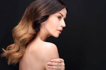 Piękne zdrowe włosy.Portret kobiety z pięknymi długimi włosami na czarnym tle