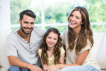 Happy couple sitting with daughter on sofa