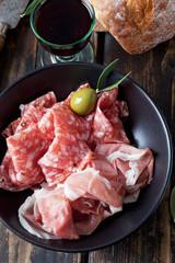 Italienischer Schinken, Salami, Glas Rotwein, Weissbrot, schwarz