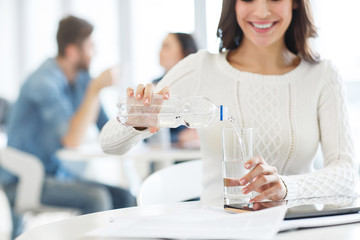 Nice woman pouring water in the glass