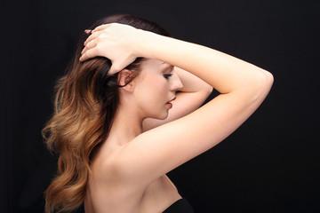 Mocne zdrowe włosy.Portret kobiety z pięknymi długimi włosami na czarnym tle