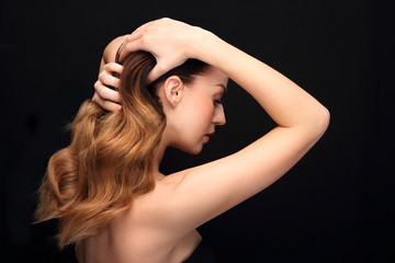 Układanie włosów.Portret kobiety z pięknymi długimi włosami na czarnym tle