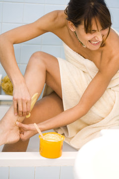 femme qui s'épile les jambes en souffrant