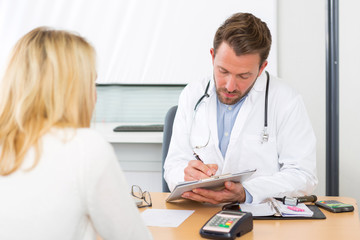 Young attractive doctor taking notes while patient speak