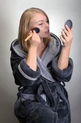 portrait of attractive woman in bathrobe doing her makeup