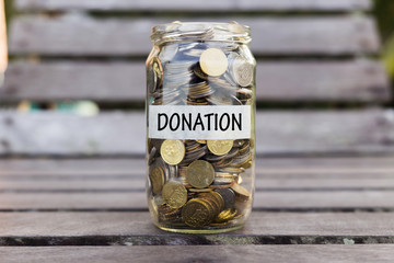Coins in the jar or glass on the wood with DONATION.  Financial concept.