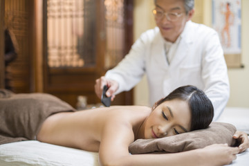 Senior Chinese doctor performing scraping therapy