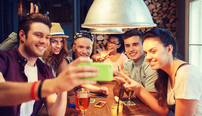 happy friends with smartphone taking selfie at bar