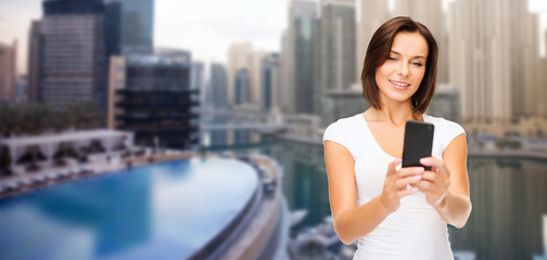 woman taking selfie by smartphone over dubai city