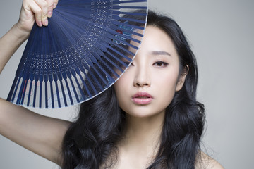 Beautiful young woman with folding fan