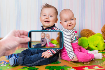Making photo of boy and girl twins by the smartphone camera