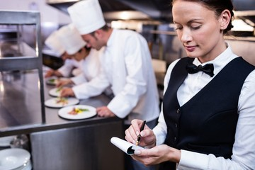 Waitress with note pad in commercial kitchen