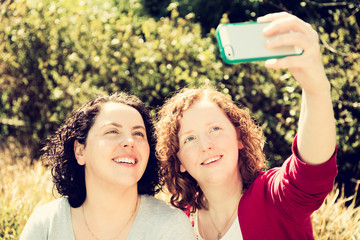 Two sisters are using their mobile Phone to take a selfie outdoors in a Sunny garden.