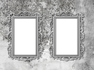 Close-up of two silver blank Baroque picture frames on weathered concrete wall background
