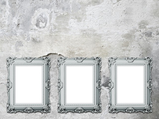 Close-up of three blue blank Baroque picture frames on cracked and scratched concrete wall background