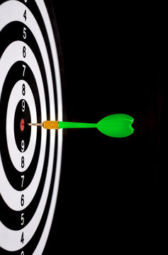 Green dart arrow hitting in the target center of dartboard with black background