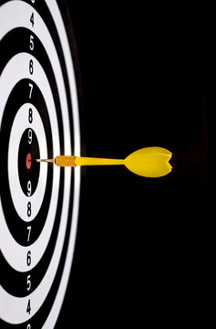 Yellow dart arrow hitting in the target center of dartboard with black background