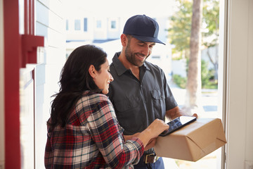 Woman Signing For Package From Courier At Home