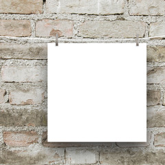 Close-up of one square blank frame hanged by pegs against grey weathered brick wall background