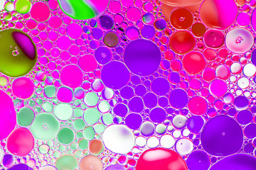 Oil drops in water on a coloured background