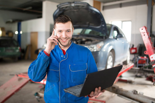 portrait of mechanic talking on mobile phone in auto repair shop. Looking at camera