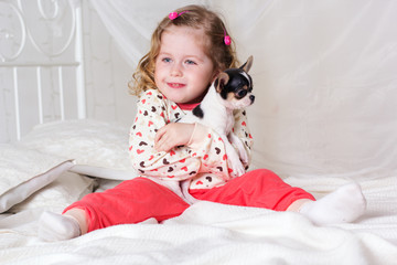 Baby girl is sitting on bed at home with dog