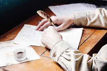 Rustic handsome young writer writing with quill on paper parchme