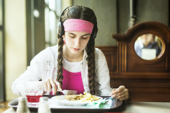 Caucasian woman wearing headphones eating in dining room