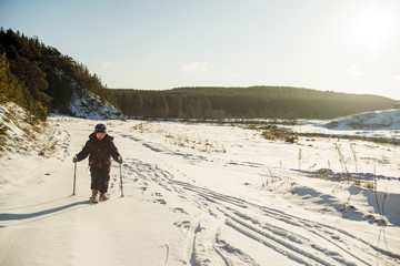 Caucasian boy cross-country skiing in snowy field