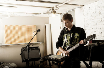 Caucasian man playing electric guitar in rock band