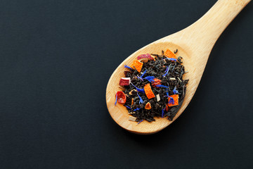 assortment of dry tea in wooden spoon, on black background