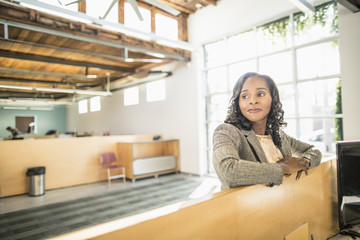 African American businesswoman standing over cubicle in office