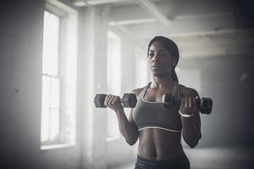 Black woman lifting weights in dark gym