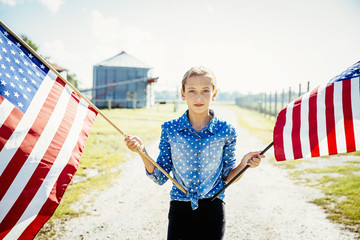 Caucasian girl waving American flags on farm