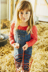 Caucasian girl collecting eggs in barn